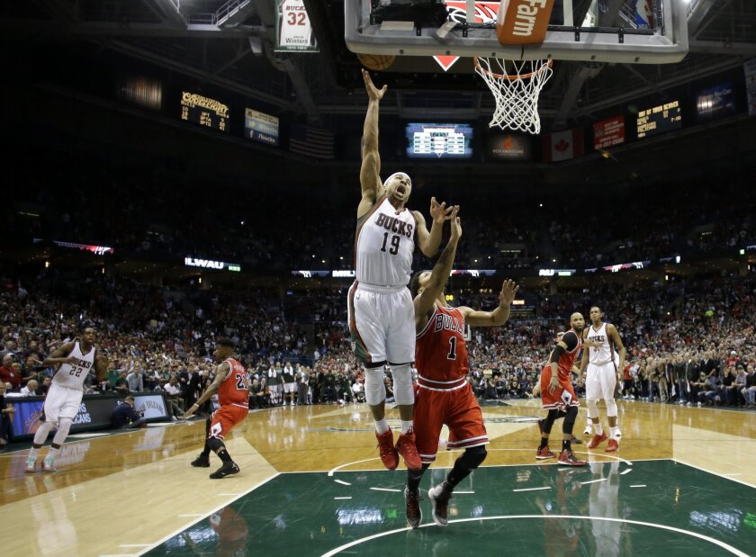 Milwaukee Bucks' Jerryd Bayless (19) puts up the game-winning shot against Chicago Bulls' Derrick Rose (1) during the second half of Game 4 of an NBA basketball first-round playoff series Saturday, April 25, 2015, in Milwaukee. The Bucks won 92-90. (AP Photo/Morry Gash)