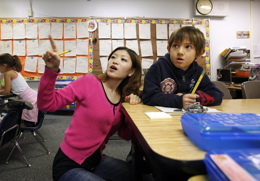 Teaching assistant Jiao Yang directs Leo Edward Martinez to the whiteboard during an assignment in Mandarin immersion at Riverview Elementary School in Lakeside.