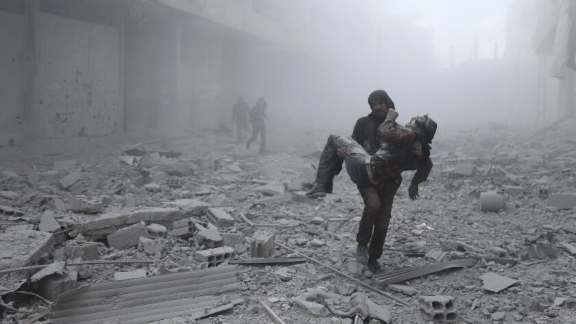 A wounded man is carried after an airstrike on the rebel-held besieged town of Arbin, on the outskirts of the Syrian capital of Damascus on Jan. 2.