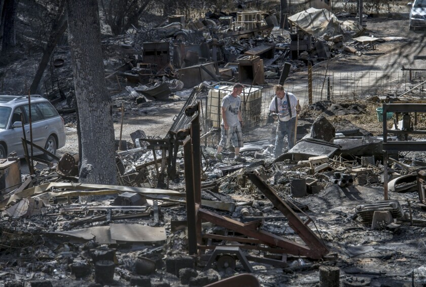 On Sept. 24, Daniel Hawkins, left, and his father, Steve Dowing, search through the remains of their Mountain Ranch, Calif., property, which was destroyed in the Butte fire.