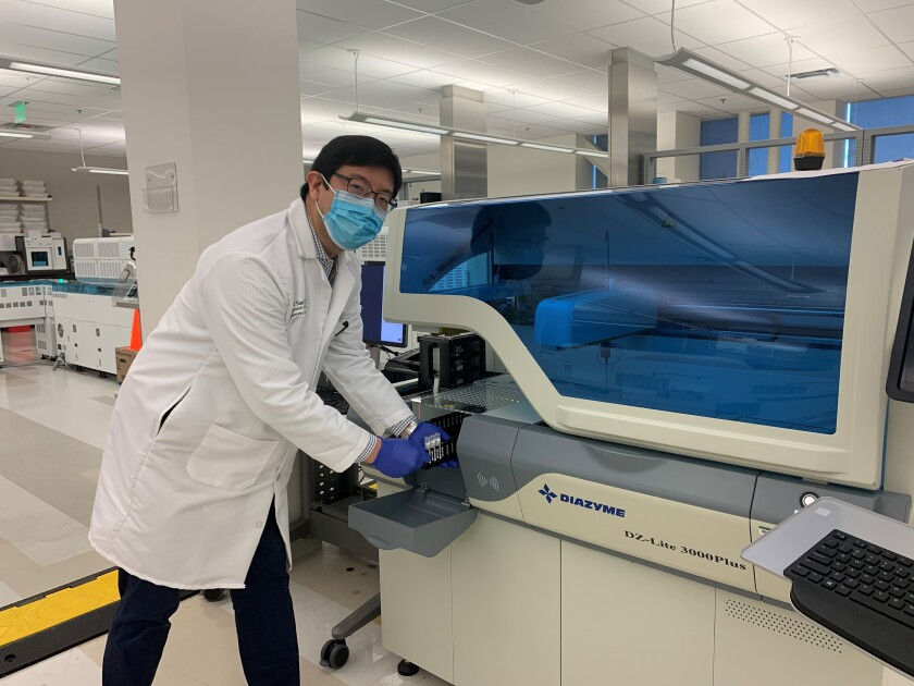 Dr. Ray Suhandynata loads samples for analysis on the Diazyme DZ-Lite 3000Plus analyzer at the UC San Diego Center for Advanced Laboratory Medicine. The instrument measures concentrations of antibodies directed against the coronavirus that causes COVID-19.