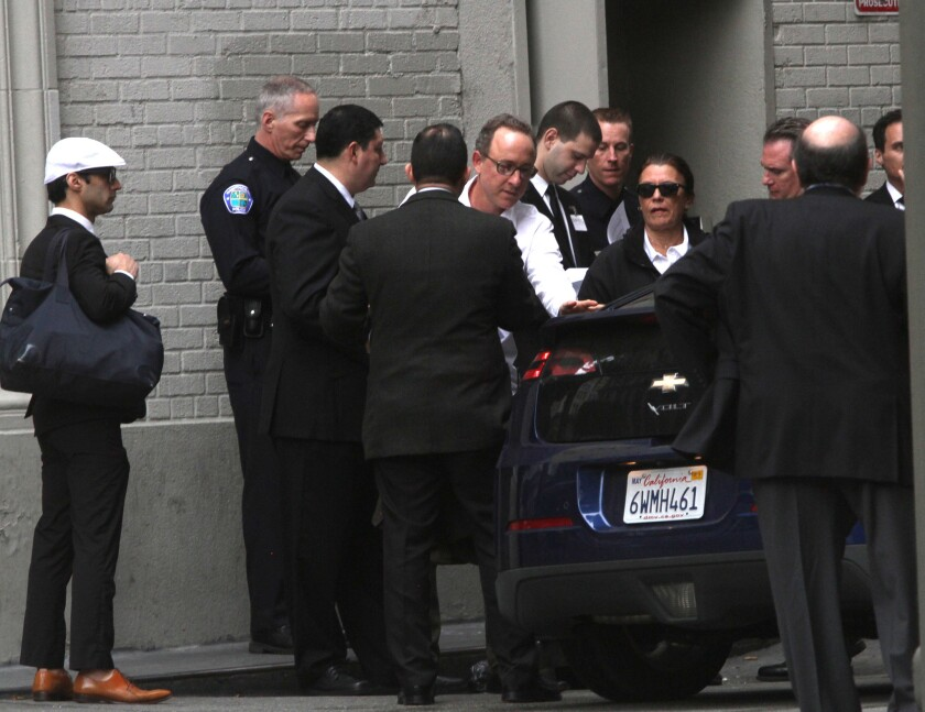 People arrive at Harlem Place alley near 7th and Spring streets for a private downtown event to hear a convicted ex-member of the Mexican Mafia speak to a group of business leaders and local police chiefs.