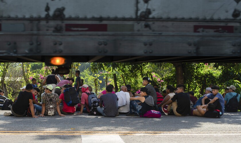 Central American migrants, part of a caravan hoping to reach the U.S. border, rest on the shoulder o