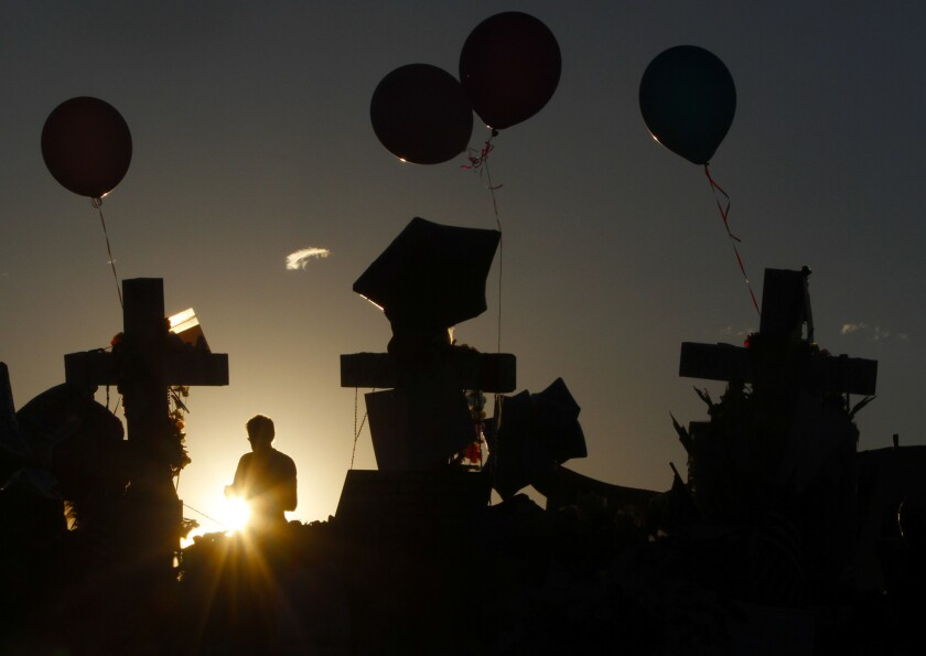 The sun rises behind a roadside memorial days after the July 2012 theater massacre in Aurora, Colo. More than three years later, the gunman has been sentenced to life in prison without the possibility of parole.