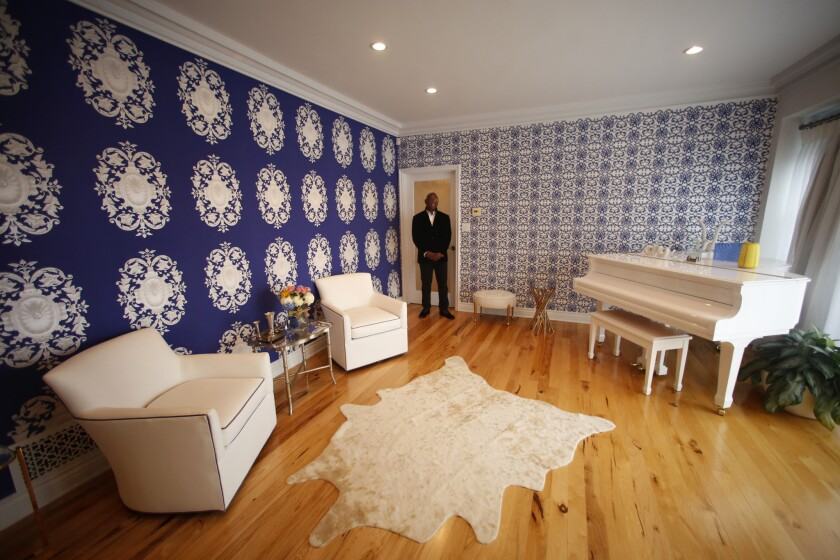 Thurmond stands in his living room, which includes two contrasting yet compatible wallpaper designs