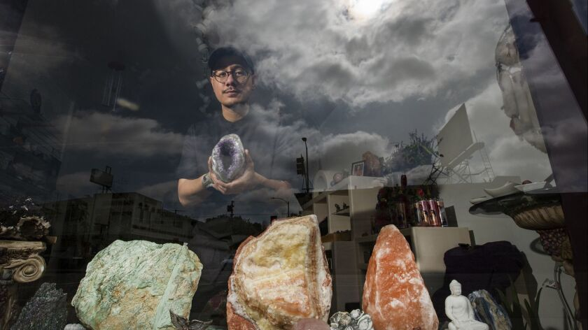 Julian Sambrano, owner of Mostly Angels L.A., photographed with crystals on display at the store. Mostly Angels has sold crystals, candles and more for 30 years in Los Angeles. Sambrano took it over in 2017.