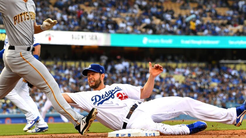 Dodgers pitcher Clayton Kershaw hangs on to the ball as he tags out Bryan Reynolds of the Pittsburgh Pirates at first base in the second inning.