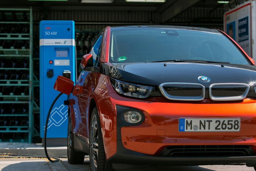 An i3 battery-powered automobile, manufactured by The Bayerische Motoren Werke AG (BMW), sits beside an electrical charging station outside the BMW manufacturing plant in Dingolfing, Germany, on Thursday, Aug. 21, 2014. BMW agreed to spend billions of euros increasing its orders of Samsung SDI Co.