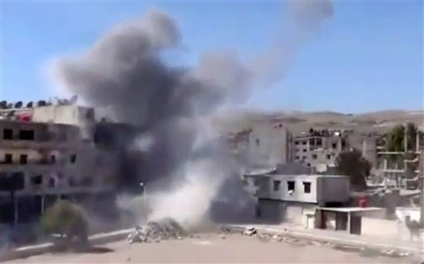 In this image taken from video obtained from the Shaam News Network, which has been authenticated based on its contents and other AP reporting, smoke rises from buildings due to heavy shelling in Maadamiyeh south of Damascus, Syria, on Thursday, March 14, 2013. (AP Photo/Shaam News Network via AP v