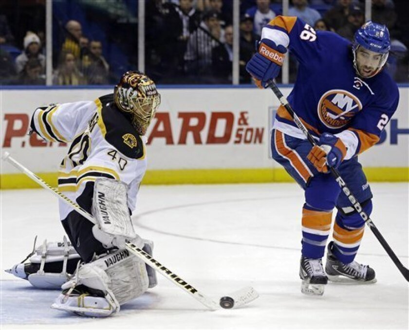 Boston Bruins goalie Tuukka Rask (40), of Finland, blocks a shot as New York Islanders left wing Matt Moulson (26) watches in the second period of their NHL hockey game at Nassau Coliseum in Uniondale, N.Y., Tuesday, Feb. 26, 2013. (AP Photo/Kathy Willens)