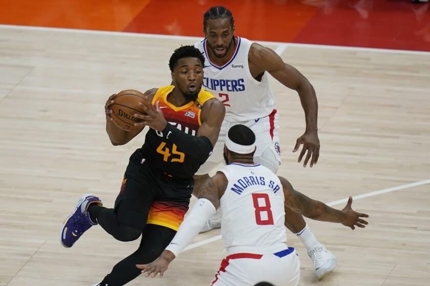 En foto del martes 8 de junio del 2021, Kawhi Leonard y Marcus Morris Sr. de los Clippers de Los Ángeles marcan al base del Jazz de Utah Donovan Mitchell en el juego 1 de la serie de segunda ronda de la Conferencia Oeste. (AP Photo/Rick Bowmer)