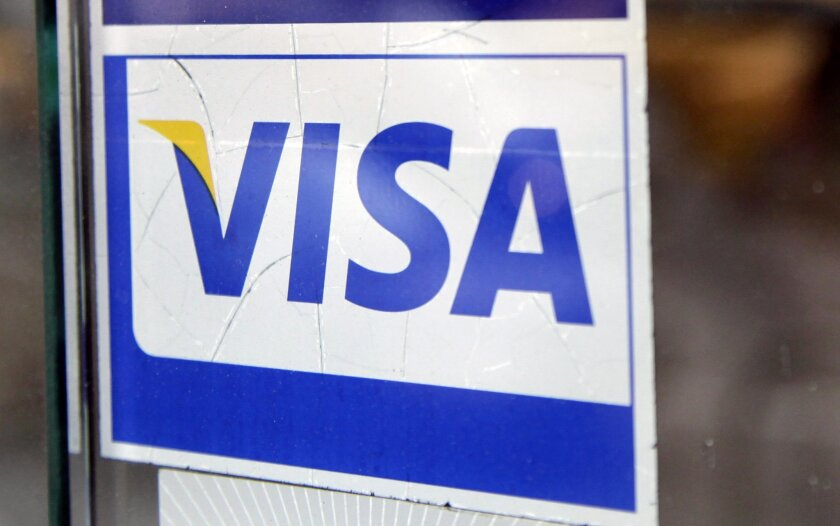 FILE - This Jan. 21, 2015 file photo shows a window decal indicating that Visa is accepted at a New York business. Visa Inc. on Thursday, April 30, 2015 said its net income fell 3 percent in the first three months of the year, hurt by the strengthening dollar and lower gas prices. (AP Photo/Mark Le