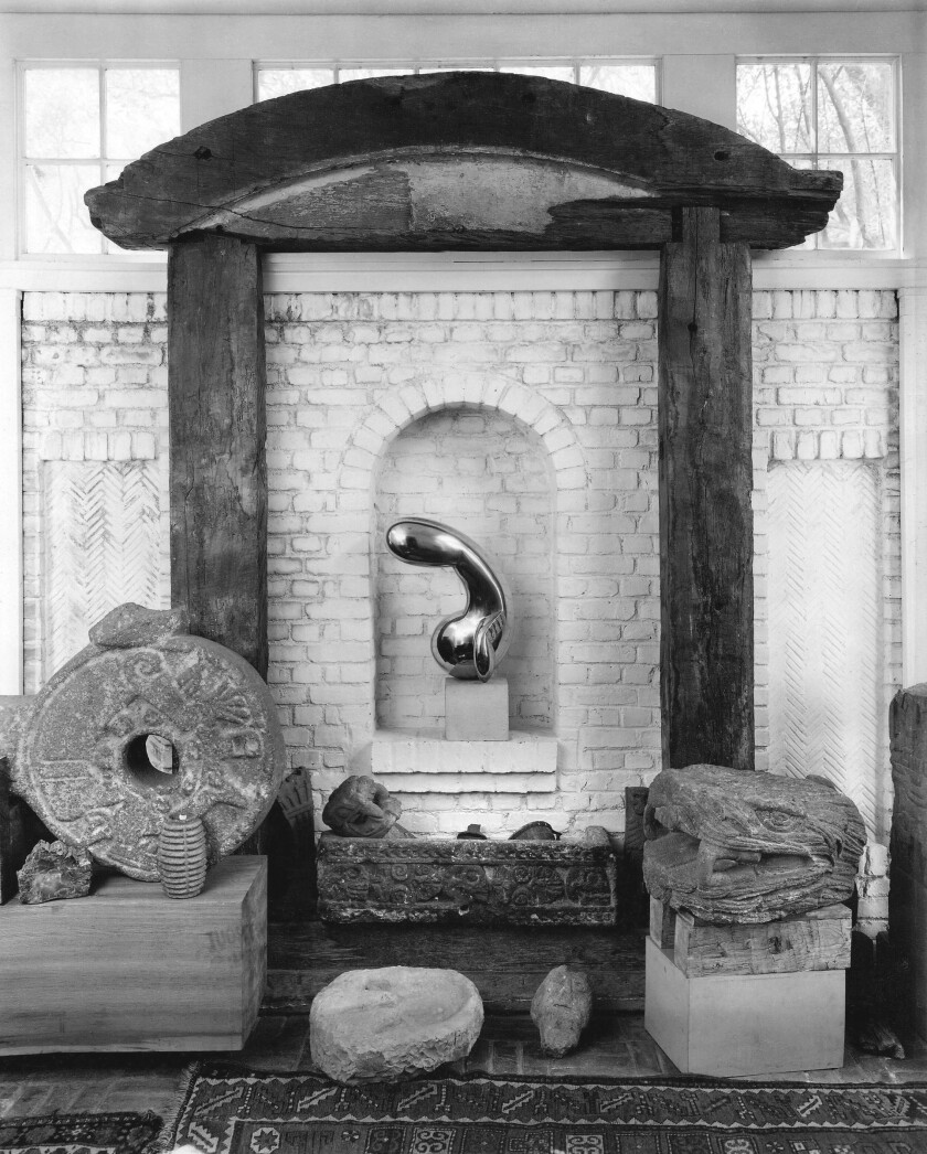 """Constantin Brancusi's sculpture """"Princess X"""" is surrounded by Aztec stone sculptures in the Arensbergs' foyer."""