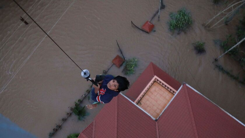 A stranded flood victim is airlifted to safety in Paravoor in the Indian state of Kerala on Aug. 18, 2018.