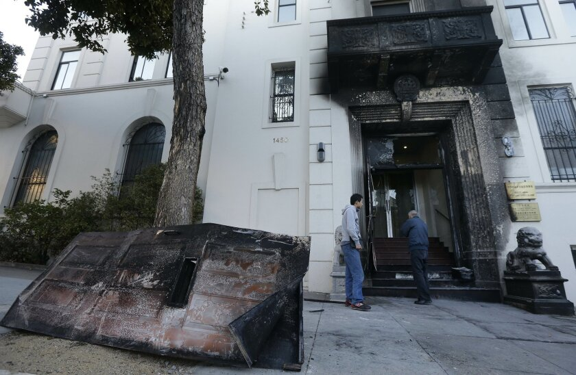 Two men look at the damage to the entrance of the Chinese Consulate in San Francisco on Thursday, Jan. 2, 2014. The consulate said in a notice on its website that a person came out of a van parked outside the compound Wednesday night with two buckets of gasoline, poured the fuel on the front of the consulate building and set it on fire. (AP Photo/Jeff Chiu)