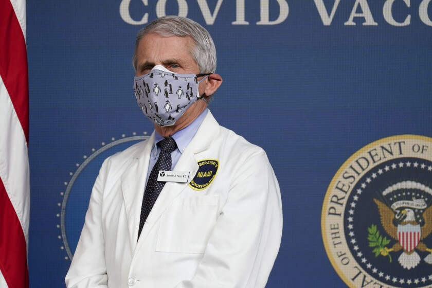 """FILE - In this Feb. 25, 2021, Dr. Anthony Fauci, director of the National Institute of Allergy and Infectious Diseases, listens as President Joe Biden speaks during an event to commemorate the 50 millionth COVID-19 shot in Washington. Fauci said Sunday, March 14, he wishes former President Donald Trump would use his popularity among Republicans to persuade his followers to get the COVID-19 vaccine. In a round of interviews on the morning news shows, Fauci lamented polling showing that Trump supporters are more likely to refuse to get vaccinated, saying politics needs to be separated from """"commonsense, no-brainer"""" public health measures. (AP Photo/Evan Vucci, File)"""