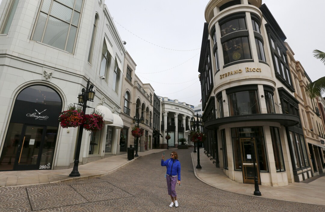 A woman uses a smartphone to record the scene along Rodeo Drive in Beverly Hills, where shops were closed and streets largely devoid of people on March 20.