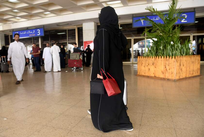 A Saudi woman rolls her suitcase at the departure hall of the Jeddah Airport on Aug. 6.