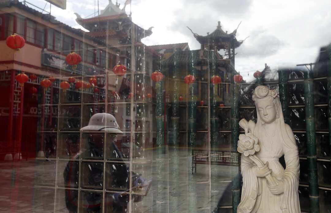 A postal carrier is reflected in the window of a shop in Chinatown, which was largely deserted.