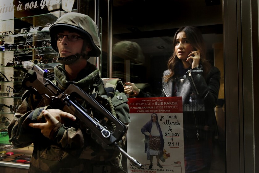 A shopkeeper stays inside her shop as soldiers guard the street where she works.