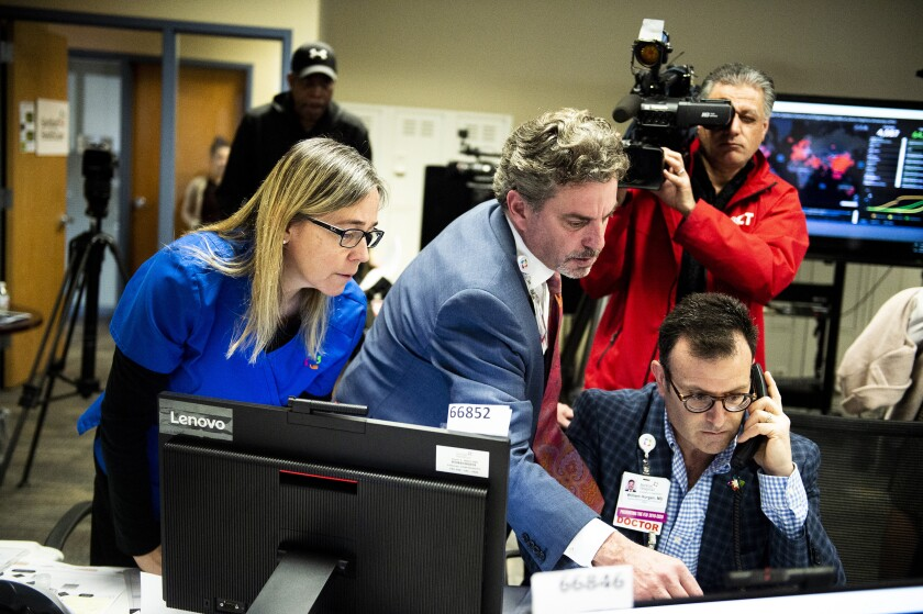 Medical professionals including Dr. Daniel Kombert, medical director for the Care Logistics Center and director for the Clinical Command Center, track data in March at the Hartford HealthCare COVID-19 Command Center in Connecticut.