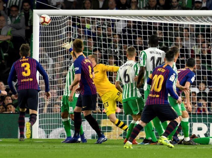El delantero argentino de FC Barcelona, Leo Messi (d), tras golpear el balón en la falta directa que ha significado el primer gol del equipo blaugrana durante el encuentro correspondiente a la jornada 28 de primera división frente al Real Betis en el estadio Benito Villamarín, en Sevilla. EFE
