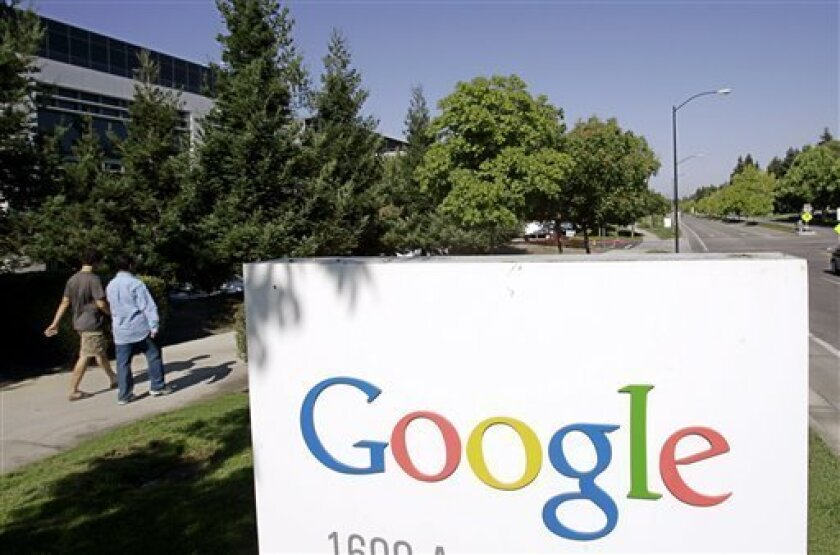 FILE - In this July 17, 2006 file photo, Google workers walk by a Google sign at company headquarters in Mountain View, Calif. Google says computer hackers in China broke into the Gmail accounts of several hundred people, including senior government officials in the U.S. and political activists. The attacks announced Wednesday, June 1, 2011 on Google's blog aren't believed to be tied to a more sophisticated assault originating from China in late 2009 and early last year. (AP Photo/Paul Sakuma, File)