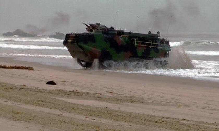 An amphibious assault vehicles plunges through the surf. Photo/AVtek Productions
