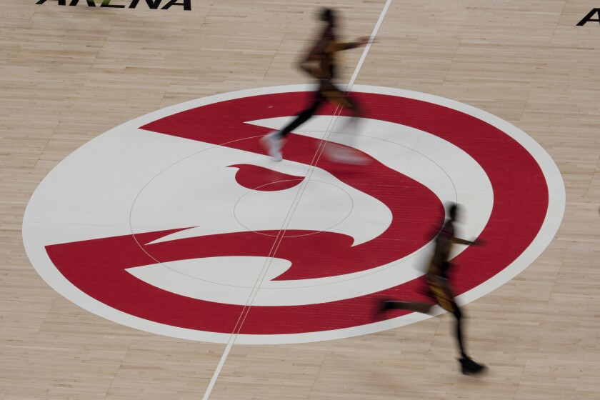 Atlanta Hawks players run past the Hawks logo during the second half of an NBA basketball game against the Houston Rockets on Sunday, May 16, 2021, in Atlanta. (AP Photo/Ben Gray)
