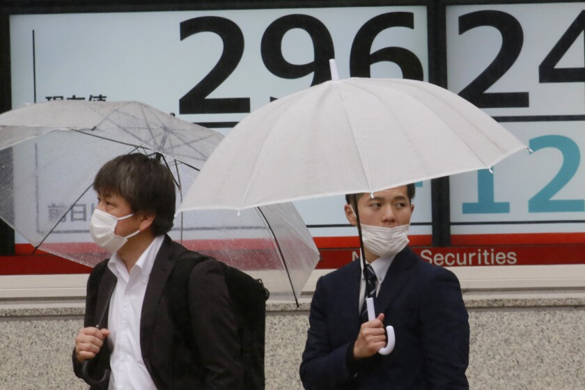 People wearing face masks stand by an electronic stock board of a securities firm in Tokyo, Wednesday, April 14, 2021. Asian stock markets rose Wednesday after Wall Street hit a high following an uptick in U.S. inflation and an order by regulators to suspend use of Johnson & Johnson's coronavirus vaccine. (AP Photo/Koji Sasahara)
