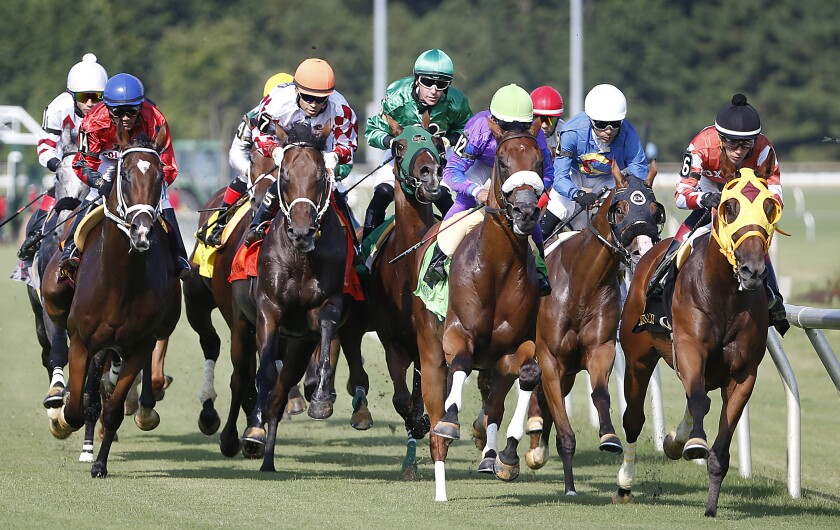 Horses head down the track during the first race on Colonial Downs' opening day of the season near New Kent, Va., on Thursday.