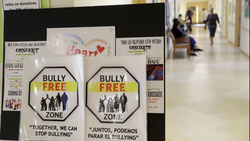 In this Friday, April 13, 2018 photo, signs promote a bully-free environment at the On Lok 30th Stre