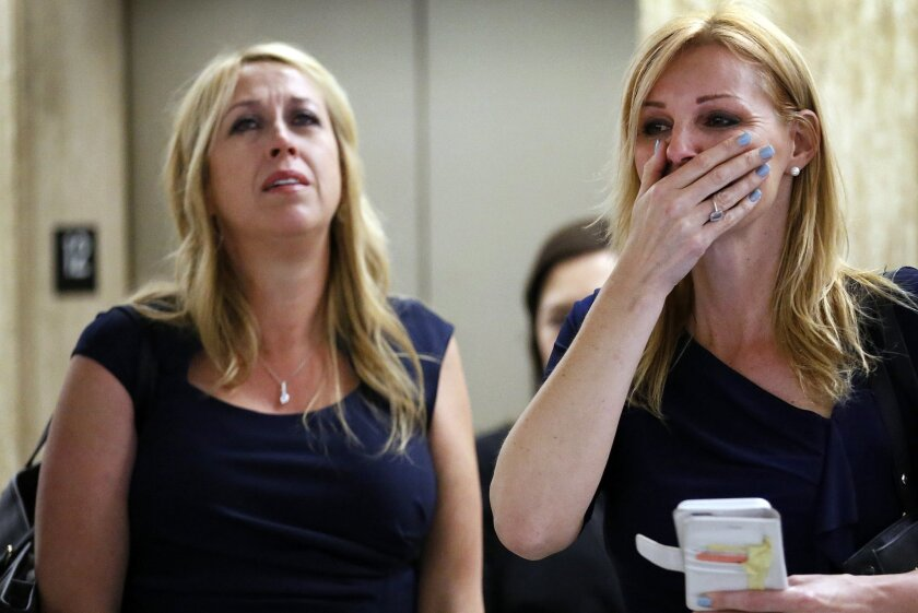 File-This May 13, 2015, file photo shows Sarah Key-Marer, left, mother of 4-year-old Lauren Sarene Key who was slain in 2000, reacting with her best friend Annette Watling, right, after Cameron Brown was found guilty on murder charges in the death of his daughter Lauren. The first-degree murder conviction in May came about a dozen years after Brown was arrested and followed two previous trials when jurors decided the death was a crime, but they couldn't agree whether it was murder or manslaughter. (Al Seib/Los Angeles Times via AP, File)