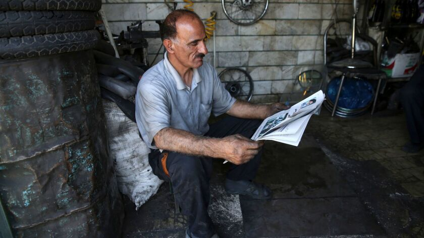 A motorcycle repairman reads a newspaper at his shop near Iran's parliament building in Tehran on Ma