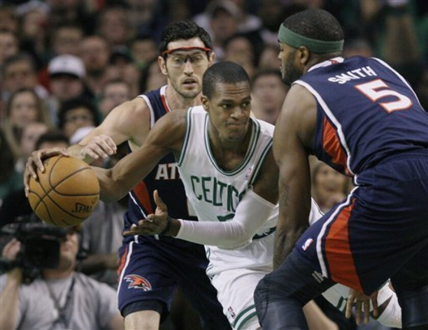 Boston Celtics guard Rajon Rondo (9) looks to pass against the double-team by Atlanta Hawks guard Kirk Hinrich and forward Josh Smith (5) during the first half of an NBA basketball game in Boston on Wednesday, April 11, 2012. (AP Photo/Elise Amendola)