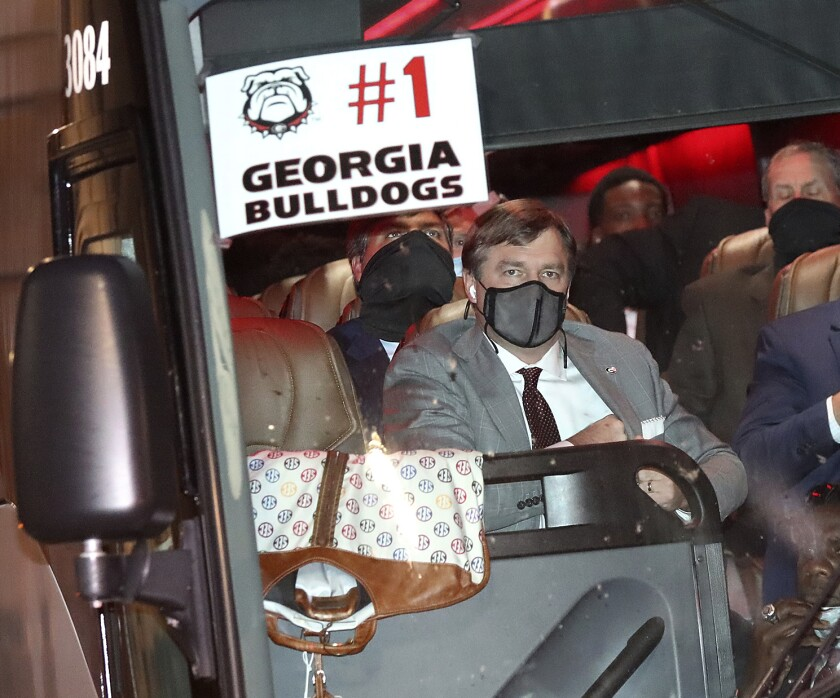 Georgia coach Kirby Smart wears a mask on one the five buses carrying the football team arrives at a hotel Friday night, Nov. 6, 2020, in Jacksonville, Fla., for Saturday's Georgia-Florida NCAA college football game. (Curtis Compton/Atlanta Journal-Constitution via AP)