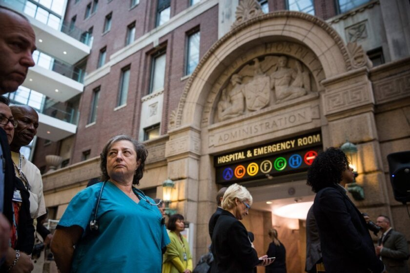 A nurse listens to a news conference about Ebola at Bellevue Hospital in New York City.