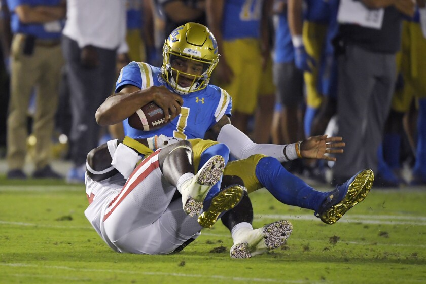 UCLA quarterback Dorian Thompson-Robinson is sacked by Oklahoma linebacker Brian Asamoah during the second half of the Bruins' 48-14 loss Saturday at the Rose Bowl.