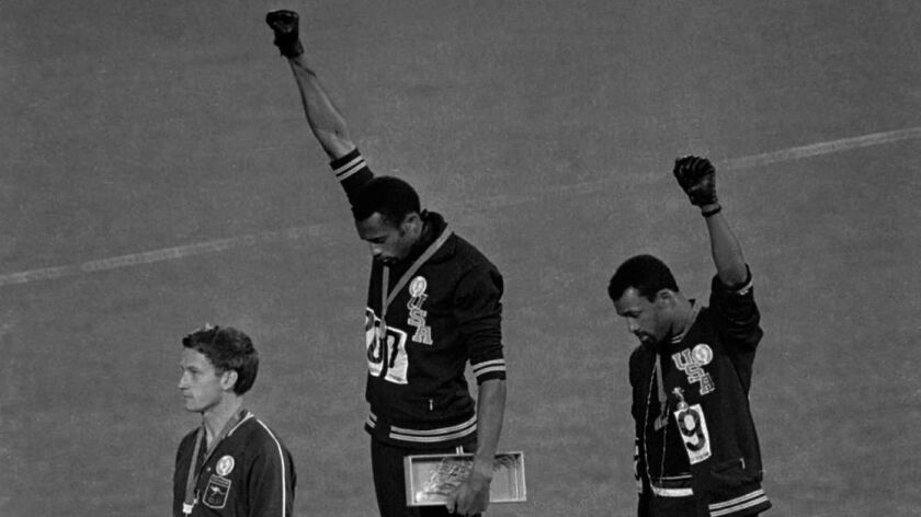 American track and field athletes Tommie Smith, center, and John Carlos, right, first and third place winners in the 200 meter race, bow their heads during the national anthem and raise their gloved fists at the Summer Olympic games in Mexico City on Oct. 19, 1968.