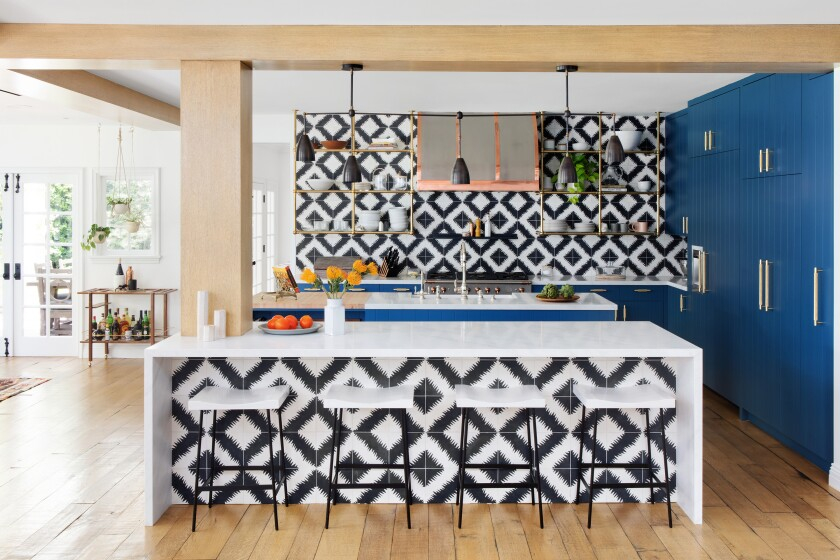 A kitchen designed for the actor Hilary Duff by Studio Life/Style camouflages refrigeration behind sapphire blue cabinetry.