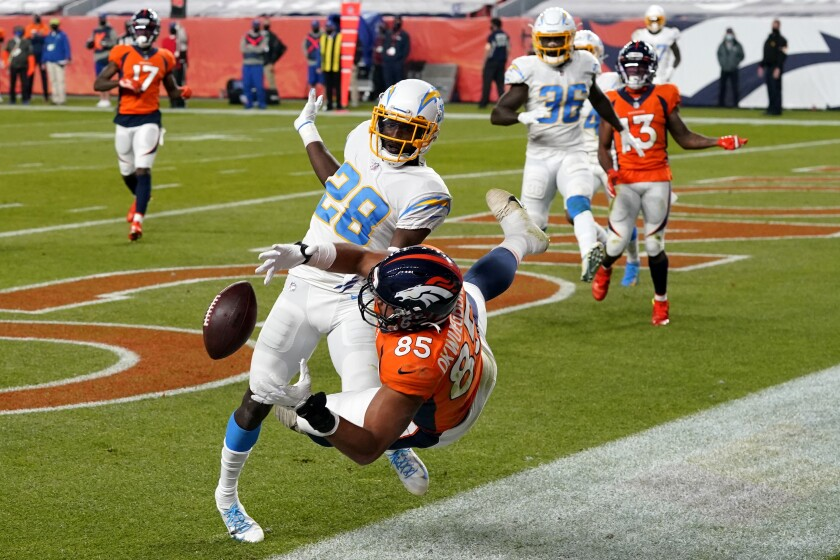 Chargers cornerback Brandon Facyson (28) commits pass interference on Denver Broncos tight end Albert Okwuegbunam.