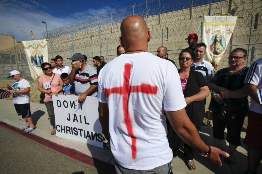 About 50 Chaldean Christians, including Aamer Moshi, foreground, hold a prayer vigil outside the U.S. Immigration and Customs Enforcement Otay Mesa detention facility, protesting the detaining of 27 undocumented Iraqi immigrants seeking asylum.