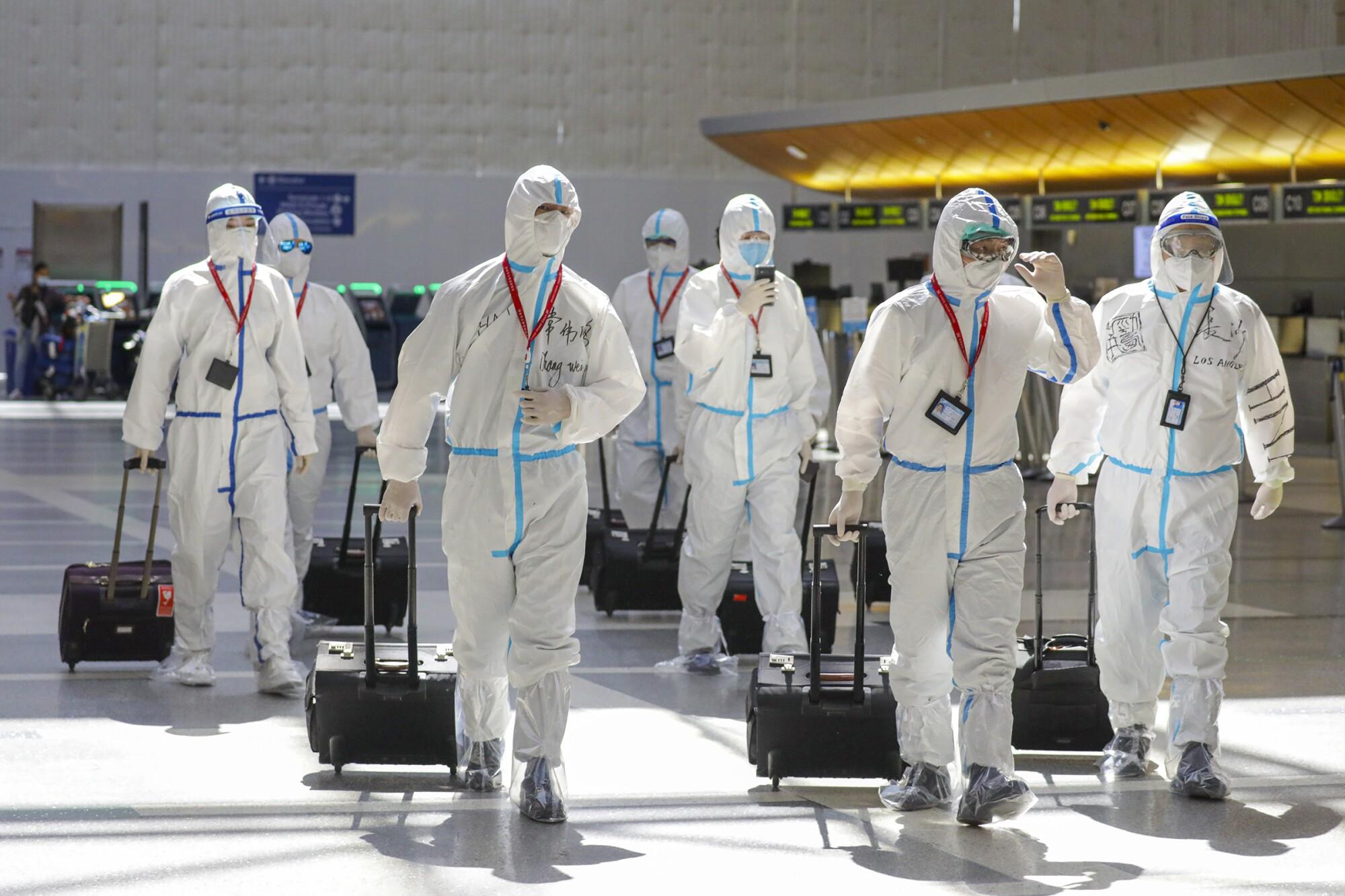 A flight crew in full biohazard suits at Tom Bradley Terminal.