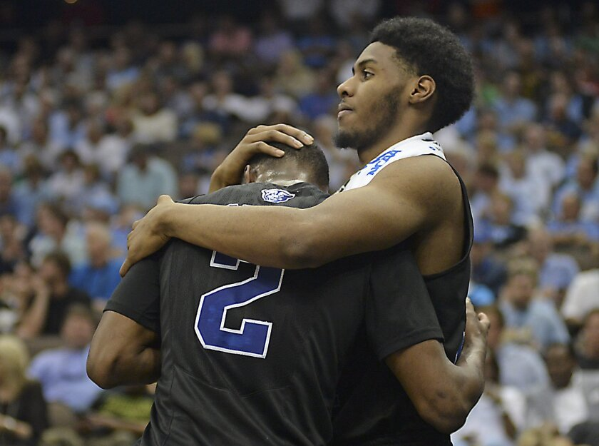Georgia State forward Markus Crider, right, consoles teammate Ryann Green (2) after losing to Xavier 75-67 in an NCAA tournament third round college basketball game, Saturday, March 21, 2015, in Jacksonville, Fla. Xavier won 75-67. (AP Photo/Rick Wilson)