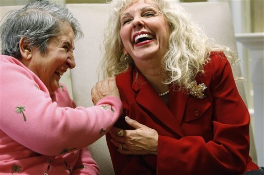 Alexis McKenzie, executive director of The Methodist Home of the District of Columbia Forest Side, an Alzheimer's assisted-living facility, right, shares a light moment with resident Catherine Peake, in Washington, Monday, Feb. 6, 2012. Dementia can sneak up on families because its sufferers are pretty adept at covering lapses early on, longer if their spouses are there to compensate. Doctors too frequently are fooled as well. Now specialists are pushing for the first National Alzheimer's Plan to help overcome this barrier to detection _ urging what's called dementia-capable primary care, more screenings for warning signs, and regular checks of caregivers' own physical and mental health. (AP Photo/Charles Dharapak)