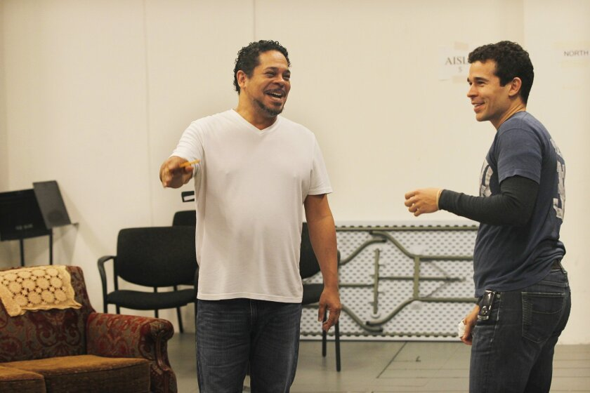 "Director Eddie Torres (left) works with Rey Lucas, who plays a former Marine named Elliot Ortiz, during rehearsals for the Old Globe Theatre production of ""Water by the Spoonful."""