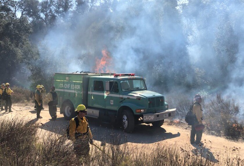 Firefighers work to halt the Sawday fire in Ramona on Friday, October 25, 2019.