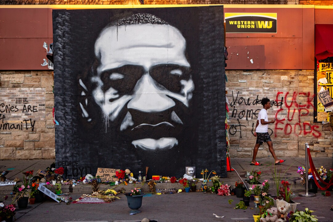 A mural of George Floyd stands on the sidewalk outside Cup Foods in South Minneapolis where he died while in police custody