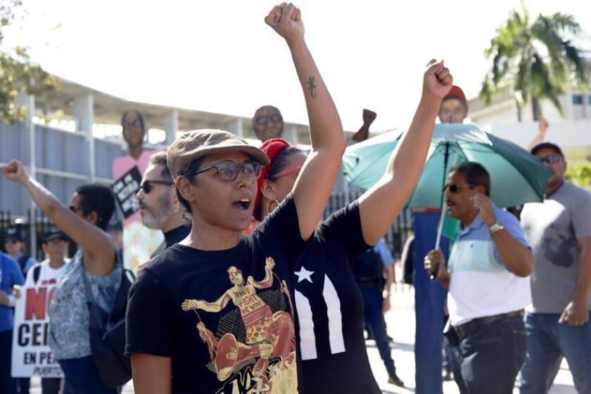 Unas personas gritan consignas durante una manifestación convocada ayer, miércoles 16 de enero de 2018, ante el Tribunal Federal en San Juan (Puerto Rico) para mostrar el rechazo al acuerdo alcanzado entre el Gobierno puertorriqueño y los acreedores Cofina. EFE