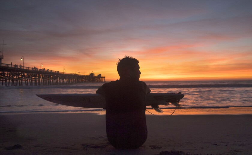 A surfer sits on the beach, holding his board, and watches the sunset.